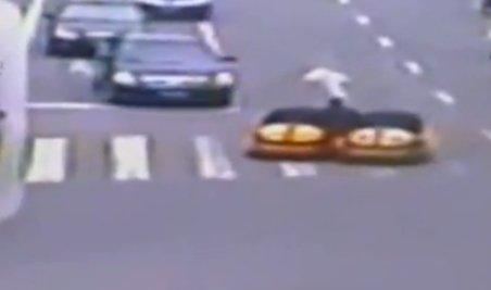 China. Un bărbat conduce simultan două maşinuţe prin traficul aglomerat