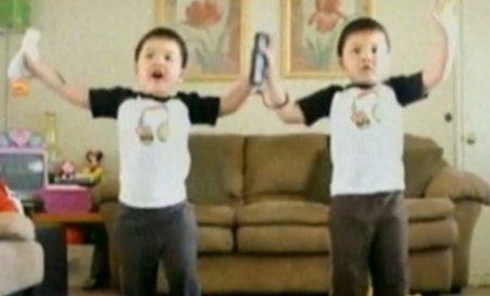 Demonstraţie de dans a doi gemeni, în timp ce se joacă pe o consolă Wii