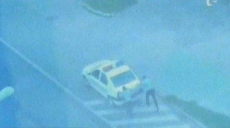 Un echipaj de poliţie îşi împinge maşina, după ce rămas fără benzină