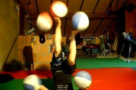 Îndemânare impresionantă. O acrobată jonglează cu cinci mingii de baschet, cu capul în jos