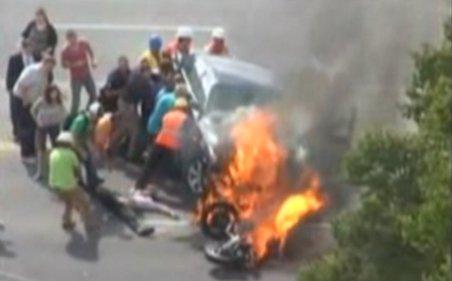 Americanii au curaj: Un motociclist inconştient este salvat de trecători. Era prins sub o maşină în flăcări