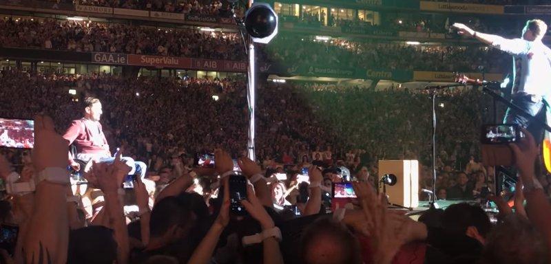 Fan Coldplay în scaun cu rotile, purtat pe brațe de mulțime până pe scenă - VIDEO