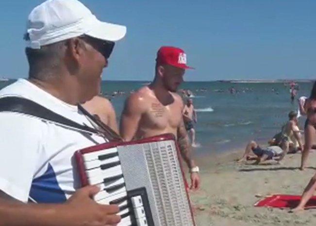 Turiștii se relaxează pe litoral. Lăutarii cântă la prosopul clientului