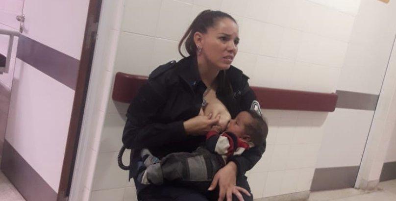 Poza cu o politista care hraneste la piept un copil a devenit virala. Motivul e dureros!