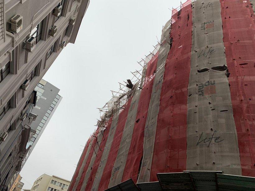 Schelă desprinsă de vântul puternic de pe fațada unui bloc din Capitală! Două mașini au fost avariate
