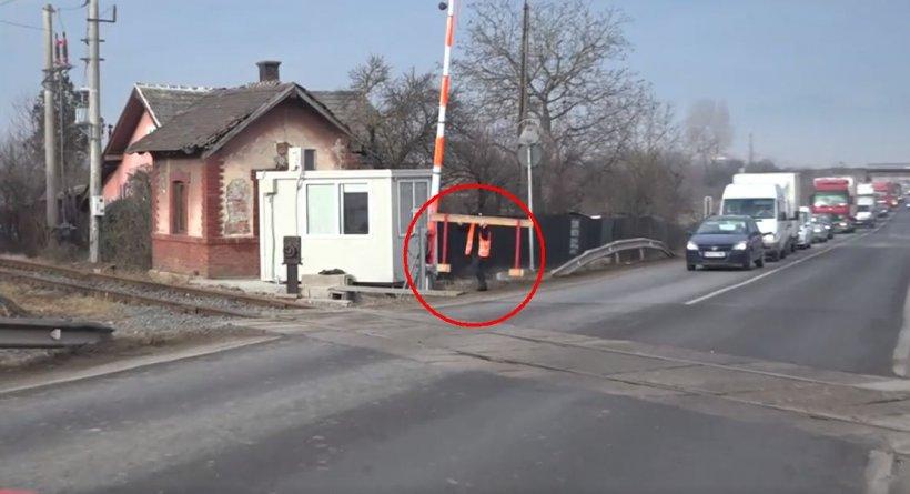 O angajată CFR cară în spate barierele de la trecerea peste calea ferată, la Hunedoara. Șoferii sunt nevoiți să aștepte zeci de minute  - VIDEO