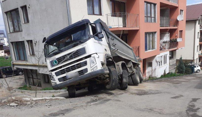 O basculantă cu 30 de tone de nisip s-a răsturnat peste parterul unui bloc, în judeţul Cluj