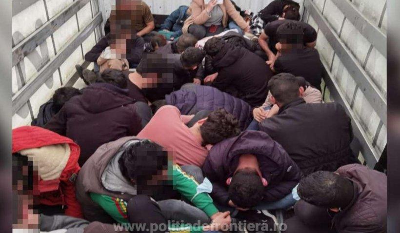 Zeci de sirieni și irakieni care încercau să traverse ilegal frontiera cu Ungaria, găsiți într-un automarfar la Vama Borș