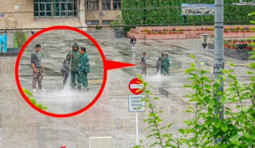 Angajați plătiți de Primăria Vaslui, fotografiați când spală granitul din centrul orașului pe ploaie