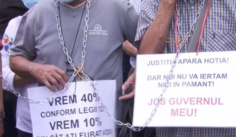 """Pensionarii protestează legați cu lanțuri în fața Palatului Cotroceni: """"Situația este sub limita suportabilității"""""""