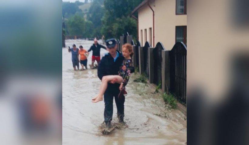 Rebeca, fetița de 10 ani cărată pe brațe de un jandarm, după ce casa i-a fost luată de ape, în județul Alba