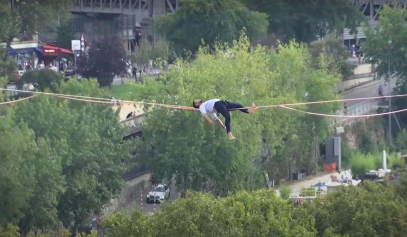 Acrobație la nivel înalt. Francezul Nathan Paulin s-a culcat pe coarda întinsă la 70 de metri înălțime, între Turnul Eiffel și Piața Trocadero