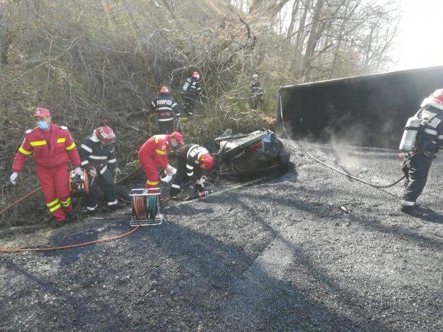 Camion încărcat cu bitum fierbinte răsturnat peste o Dacie