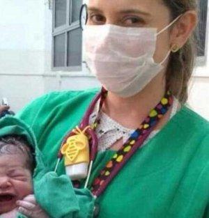 Asistenta a pozat nou nascutul imediat dupa nastere! Insa de disperare sa prinda cadrul perfect, nu s-a mai uitat ce se vede in spate! Fotografia a facut inconjurul lumii